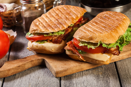 Toasted ciabatta sandwich with smoked bacon, cheese and tomato on cutting board