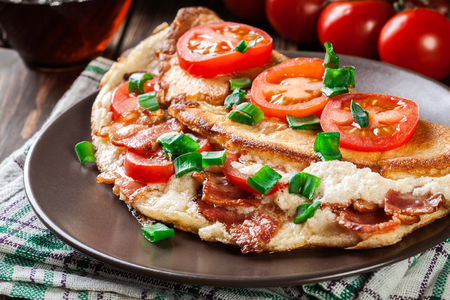 Omelette with bacon and tomatoes on brown plate.