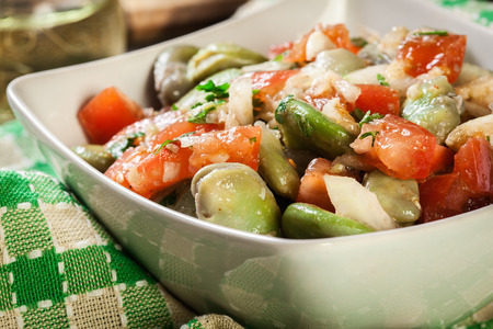 Broad bean salad with tomatoes, onion and olive in white bowl Stok Fotoğraf