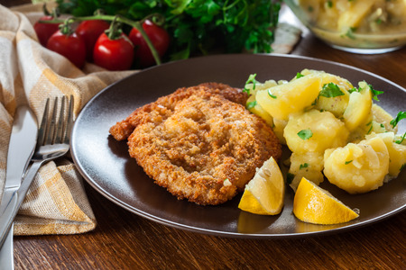 Homemade breaded viennese schnitzel with potato salad on a plate