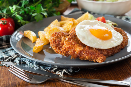 Breaded viennese schnitzel with fried agg, baked potatoes and salad. European cuisine