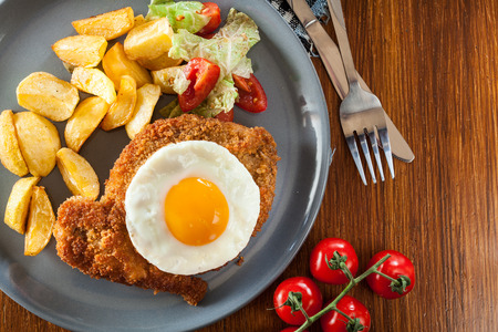 Breaded viennese schnitzel with fried agg, baked potatoes and salad. European cuisine. Top view Stock Photo
