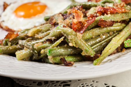 Healthy sauteed green beans with bacon and fried egg on a white plate