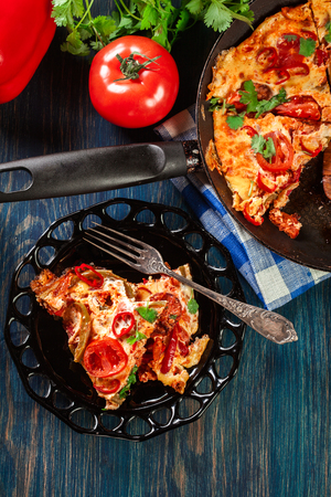 Portion of frittata with eggs, sausage chorizo, red pepper, green pepper, tomatoes, cheese and chili in a plate on wooden table. Italy cuisine. Top view. Reklamní fotografie