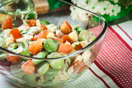 Broad bean salad with tomatoes, onion and olive in glass dish Imagens