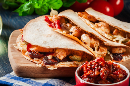 Mexican Quesadilla with chicken, sausage chorizo and red pepper served with salsa Stock Photo