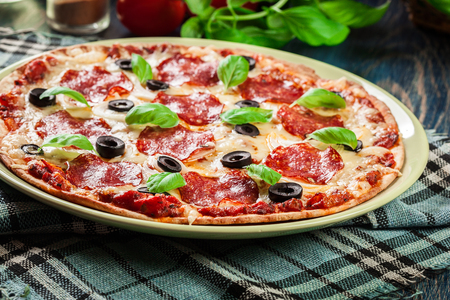 Pizza pepperoni with olives served on a plate Stock Photo