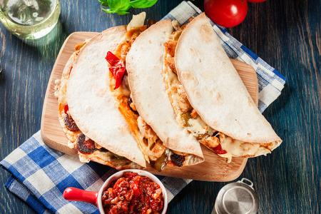 Mexican Quesadilla with chicken, sausage chorizo and red pepper served with salsa. Top view