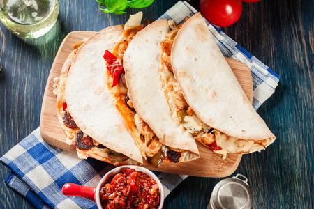Mexikanische Quesadilla mit Hühnchen, Wurst-Chorizo und rotem Pfeffer, serviert mit Salsa. Draufsicht