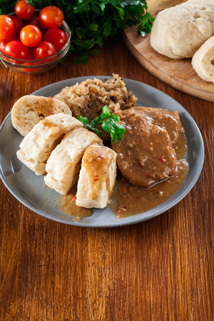 Pork loin in gravy with bread dumplings and sauerkraut. Czech cuisine Stock Photo