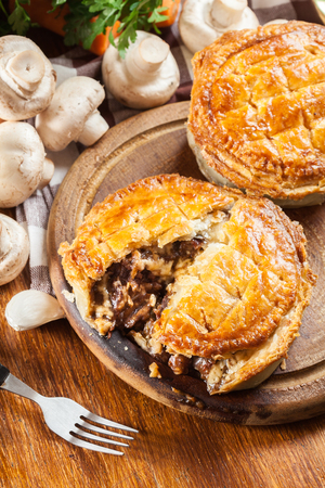 Fresh beef stew pie on a cutting board. Meat in puff pastry Stockfoto - 100764355