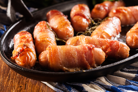 Pigs in blankets. Mini sausages wrapped in smoked bacon in baking dish Stock Photo