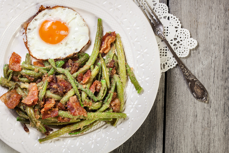 Healthy sauteed green beans with bacon and fried egg on a white plate. Top view