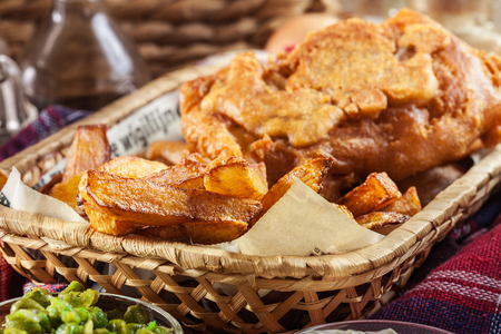 Traditional fish in beer batter and chips served on basket