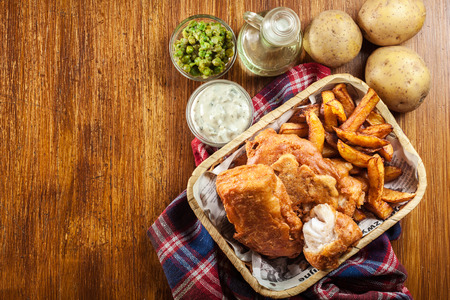 Traditional fish in beer batter and chips served on basket. Top view Stock Photo