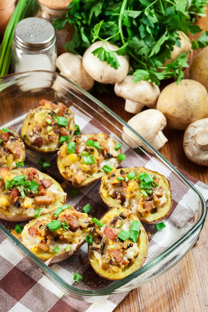 Baked potatoes in jacket stuffed with bacon, mushrooms and cheese. Dish served in baking dish Banco de Imagens