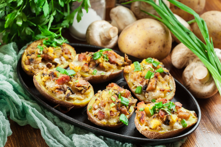 Baked potatoes in jacket stuffed with bacon, mushrooms and cheese. Dish served in baking dish 免版税图像