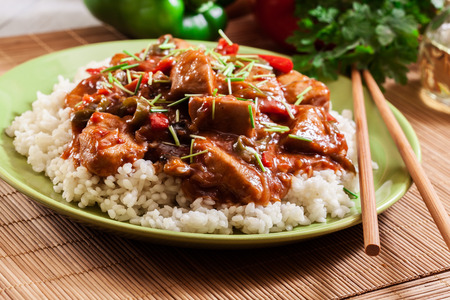 Delicious chicken in sweet and sour sauce served with rice Фото со стока