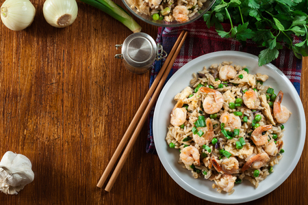 Fried rice with shrimp and vegetables served on a plate. Popular chinese dish. Top view