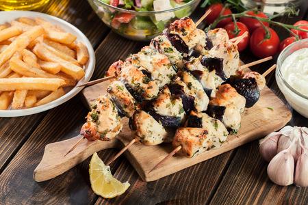 Chicken Souvlaki with pita bread and tzatziki sauce. Greek dish on chopping board