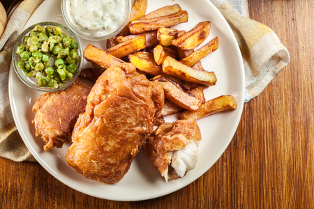 Traditional fish in beer batter and chips with green pea and tartar sauce.Top view