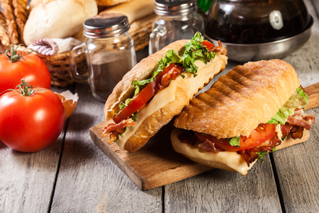 Toasted ciabatta sandwich with smoked bacon, cheese and tomato on cutting board Stock Photo