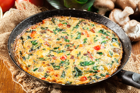 Frittata made of eggs, mushrooms and spinach on a frying pan. Italian cuisine Stock Photo