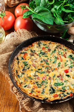 Frittata made of eggs, mushrooms and spinach on a frying pan. Italian cuisine Фото со стока