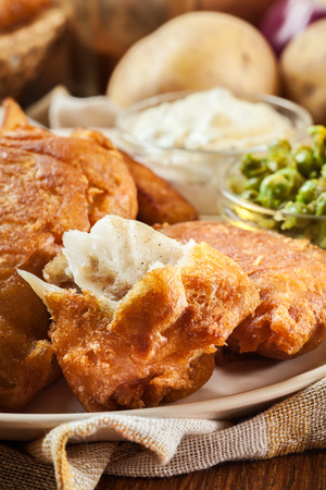 Traditional fish in beer batter and chips with green pea and tartar sauce