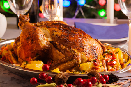 Baked whole chicken for Christmas dinner on festive table Imagens