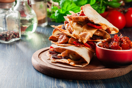 Stack of quesadillas with chicken, sausage chorizo and red pepper served with salsa. Mexican cuisine. Side view Stock Photo