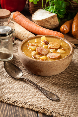 Wooden bowl of split pea soup with sausage, bacon and potatoes