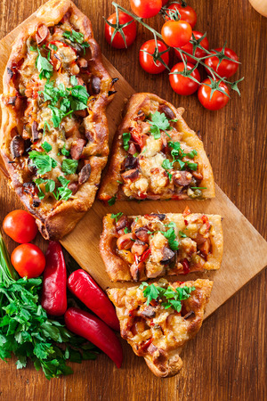 Sliced traditional Turkish pide with meat and vegetables on cutting board. Top view Stock Photo