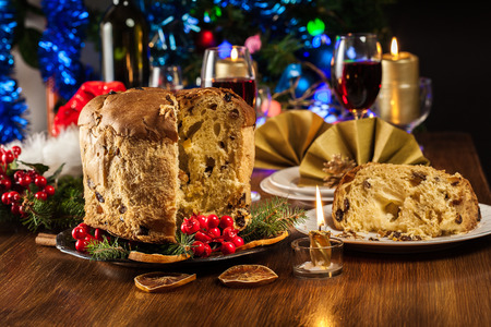 Christmas panettone cake with raisins and fruits. Traditional Italian dish Фото со стока