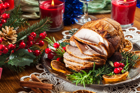Roasted pork ham served with baked potatoes. Concepts of holiday food. Stock Photo