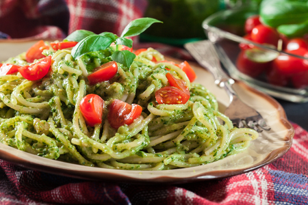 Vegetarian pasta spaghetti with basil pesto and cherry tomatoes. Italian dish Archivio Fotografico