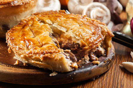 Fresh beef stew pie on a cutting board. Meat in puff pastry