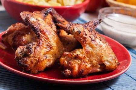 Gustose ali di pollo al forno su un piatto servito con patatine fritte Archivio Fotografico