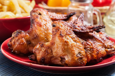 Tasty baked chicken wings on a plate served with french fries
