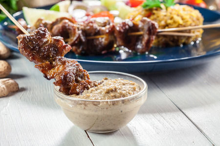 Traditional pork satay with peanut sauce and vegetables. Indonesian and Malaysian food. Stock Photo