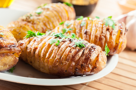 Hasselback potatoes. Baked potatoes with cheese and herbs. Swedish cuisine