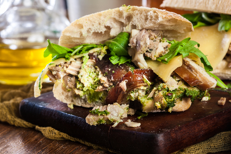 Italian porchetta sandwich. Ciabatta with rolled pork belly Imagens