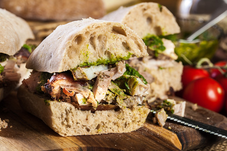 Italian porchetta sandwich. Ciabatta with rolled pork belly Imagens