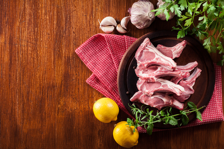 Raw fresh lamb chops on wooden cutting board. Food and drink concept