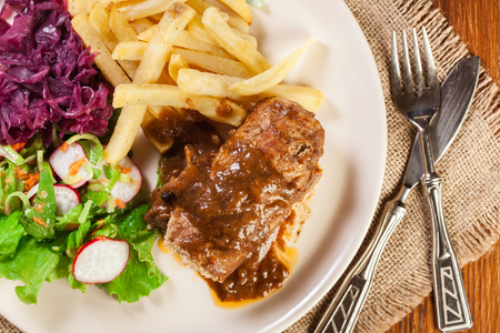 Pork roulade with french fries with salad on a plate