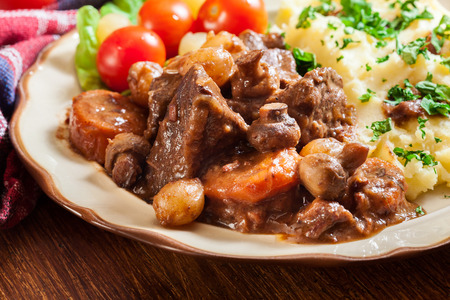 Dinner or lunch with beef Bourguignon stew served with mashed potatoes on a plate. Imagens