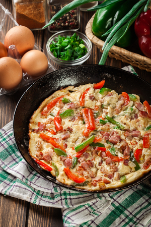 Fresh omelette with bacon and bell pepper on a pan