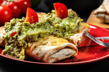 Mexican chimichanga with guacamole dip on a red plate