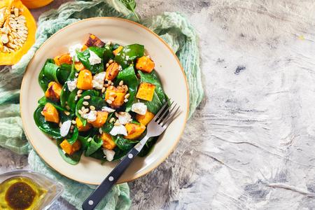 Insalata di zucca arrosto con spinaci, feta e pinoli. Piatto autunnale