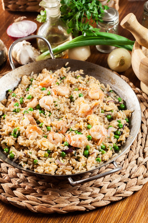 Fried rice with shrimp and vegetables on a frying pan. Popular chinese dish. Top view